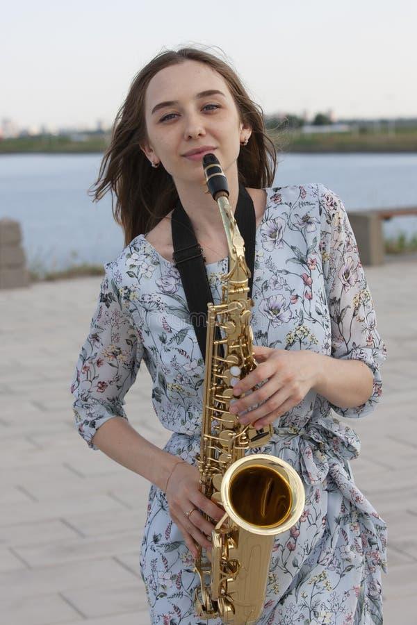 Saxofonista bonito novo com o saxofone - exterior na natureza fotos de stock