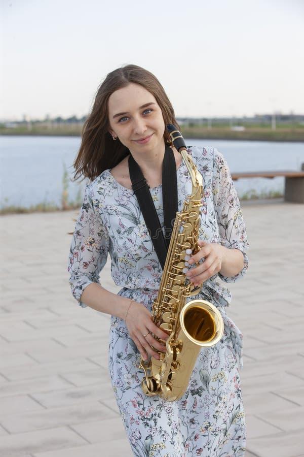Saxofonista bonito novo com o saxofone - exterior na natureza fotos de stock royalty free
