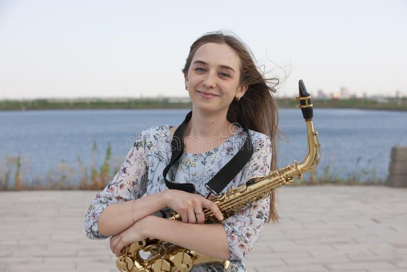 Saxofonista bonito novo com o saxofone - exterior na natureza imagem de stock