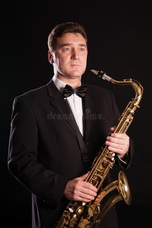 Saxofonista em um fundo preto fotografia de stock royalty free