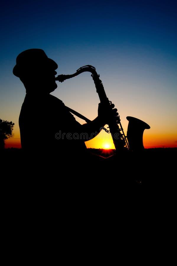 Saxofonista no por do sol 2 foto de stock