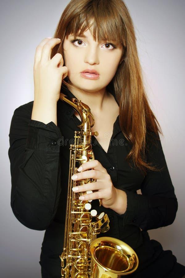 saxofonkvinnabarn arkivfoto
