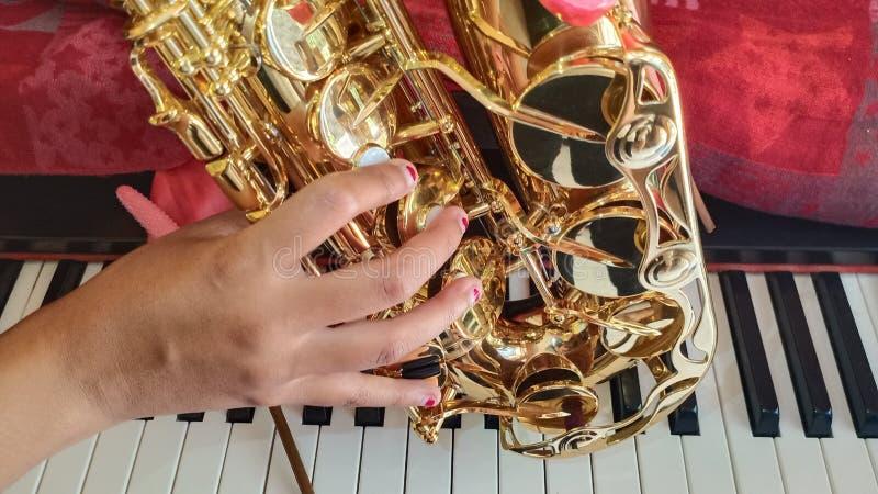 Saxofoon, meisjeshand en de piano stock afbeelding