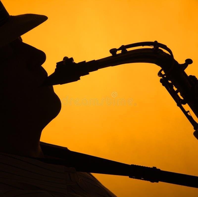 Saxofoon Performae die ik op Goud heb gesilhouetteerd stock afbeelding