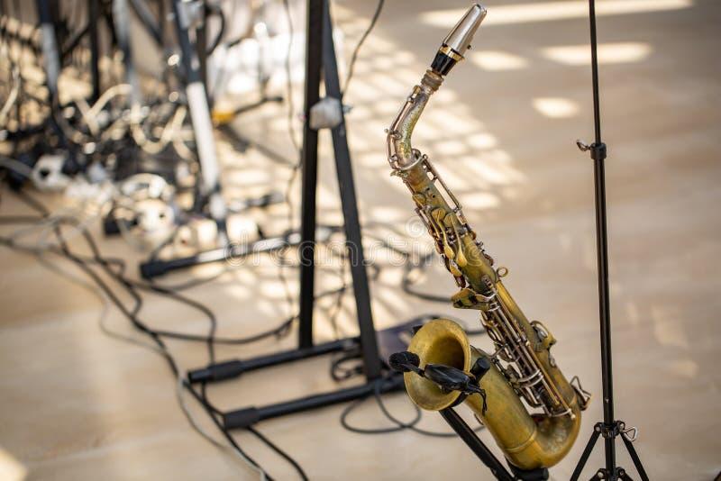 Saxofoon van gouden kleurentribunes op het rek op het stadium stock afbeelding