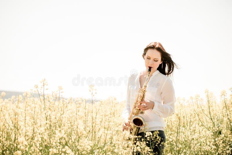 Saxophone παιχνιδιού γυναικών στη φύση στοκ εικόνα με δικαίωμα ελεύθερης χρήσης