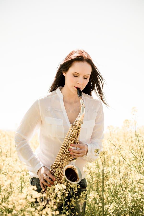 Saxophone παιχνιδιού γυναικών στη φύση στοκ φωτογραφία με δικαίωμα ελεύθερης χρήσης