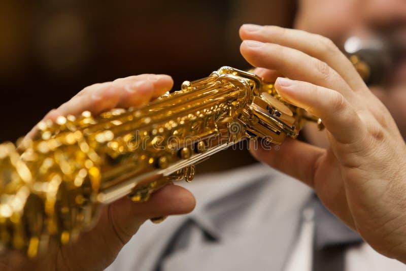Saxophone στα χέρια ενός μουσικού στοκ φωτογραφία