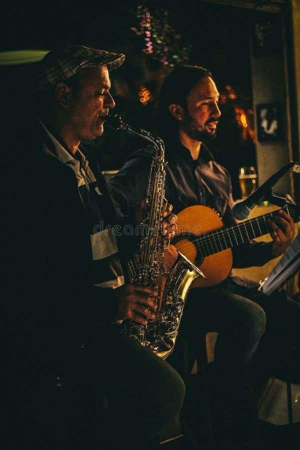 Δύο άτομα που παίζουν Saxophone και την ακουστική κιθάρα κατά τη διάρκεια της νύχτας στοκ εικόνες