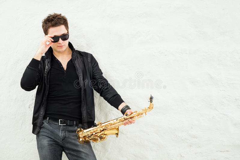 Saxophone. Young man playing sax laening against a wall stock image