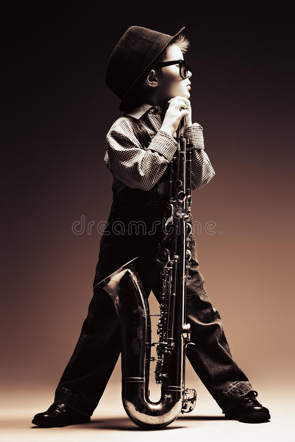 Saxophone. Portrait of a cute little boy jazzman playing his saxophone. Retro style stock photo