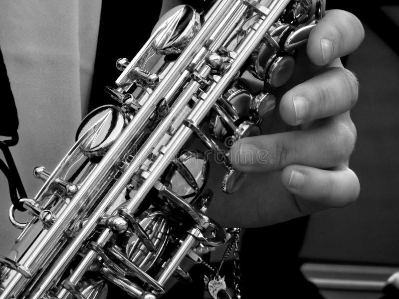 Εκμετάλλευση Saxophone προσώπων στην γκρίζα φωτογραφία κλίμακας στοκ εικόνες