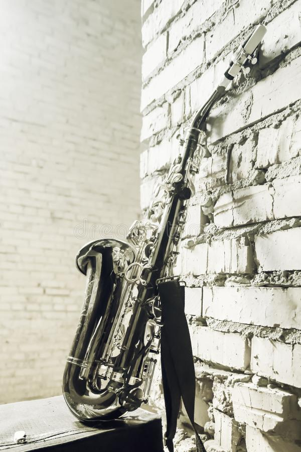 Saxophone On The Brick Wall Background - Vintage Toned Image royalty free stock photography