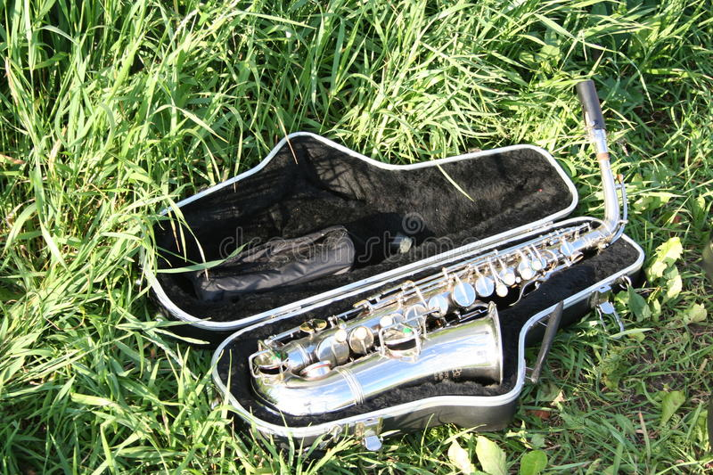 Saxophone in case. Silver saxophone in black case laying on the grass stock images