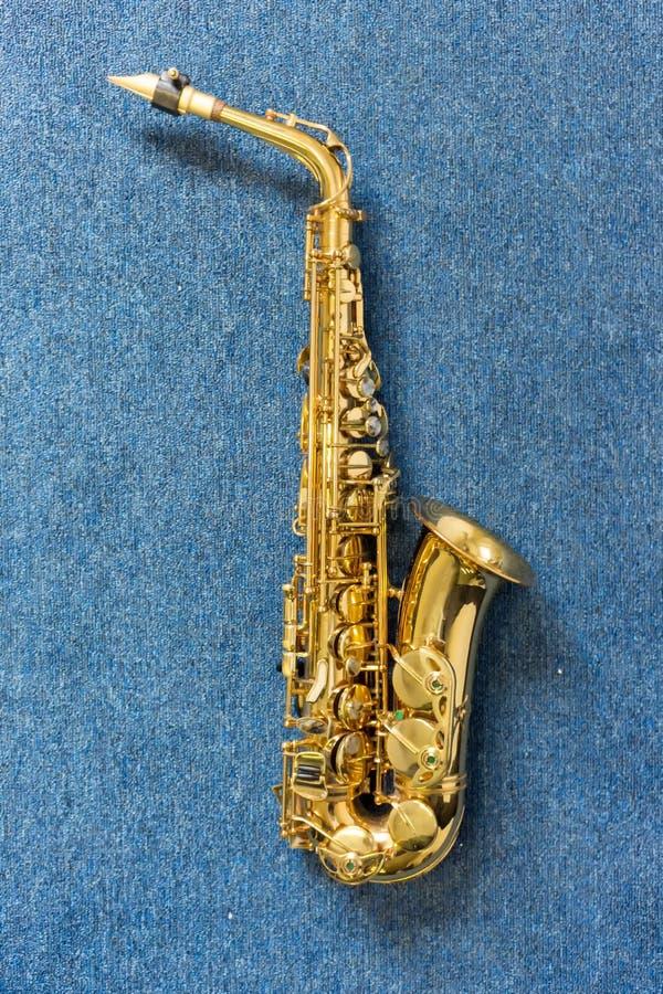Saxophone de Golden de musicien de jazz sur le mur bleu photographie stock