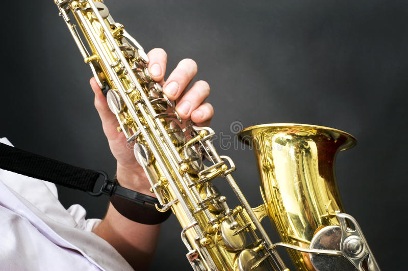 Saxophone details. Details of a shiny brass saxophone being played stock image