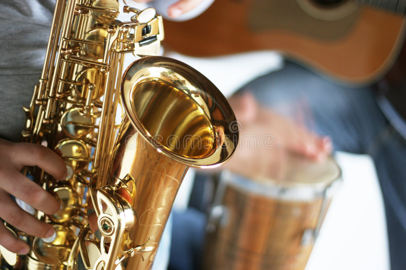 Saxophone, drums and guitar. Closeup of a saxophone player with drums and guitar in the background - focus only on the part in the foreground of the saxophone royalty free stock images