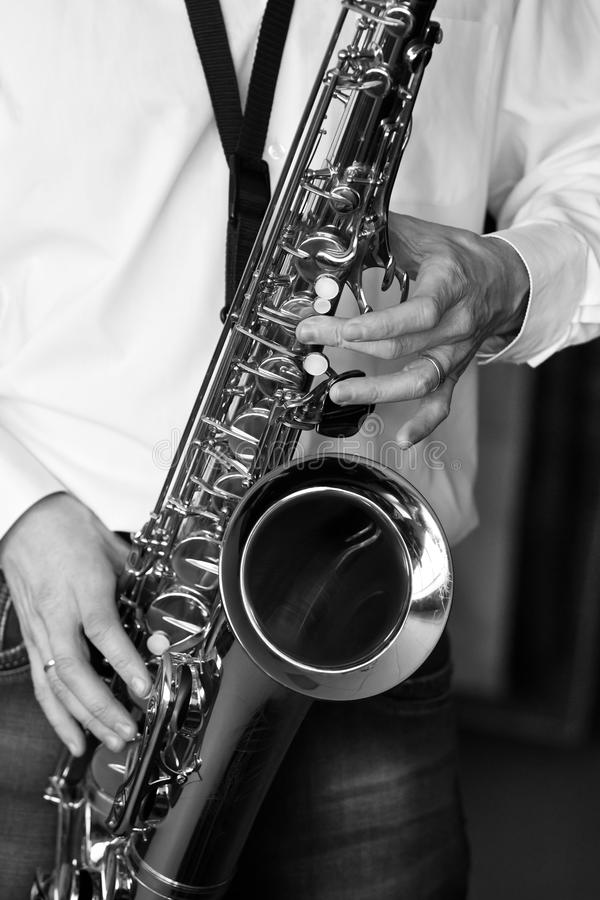 Saxophone in the hands of a musician. Closeup in black and white stock images
