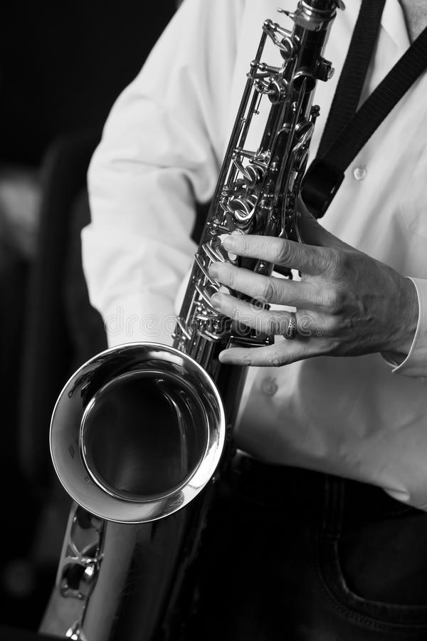 Saxophone in the hands of a musician. Closeup in black and white stock image