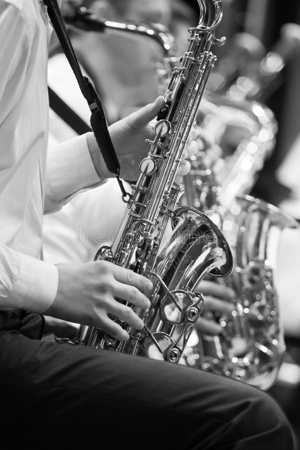Saxophone in the hands of a musician. In an orchestra in black and white royalty free stock photography