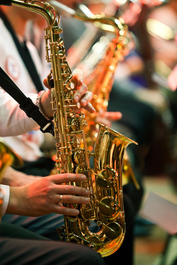 Saxophone in the hands of a musician. In an orchestra closeup stock photos