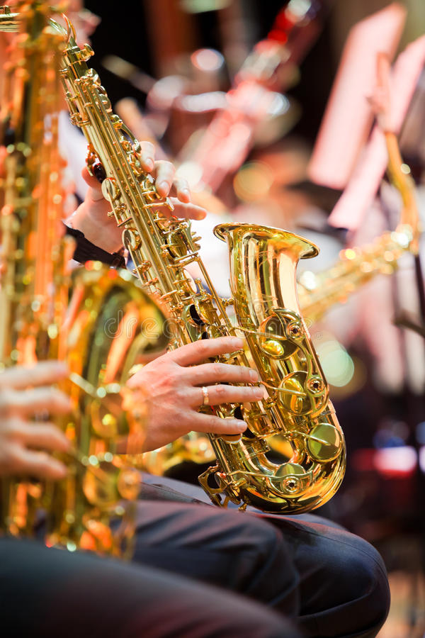 Saxophone in the hands of a musician. Hands musician playing the saxophone in a jazz band royalty free stock photo