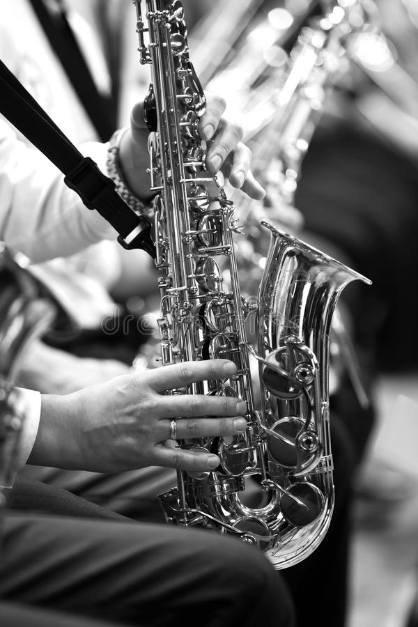 Saxophone in the hands of a musician. In an orchestra in black and white royalty free stock images