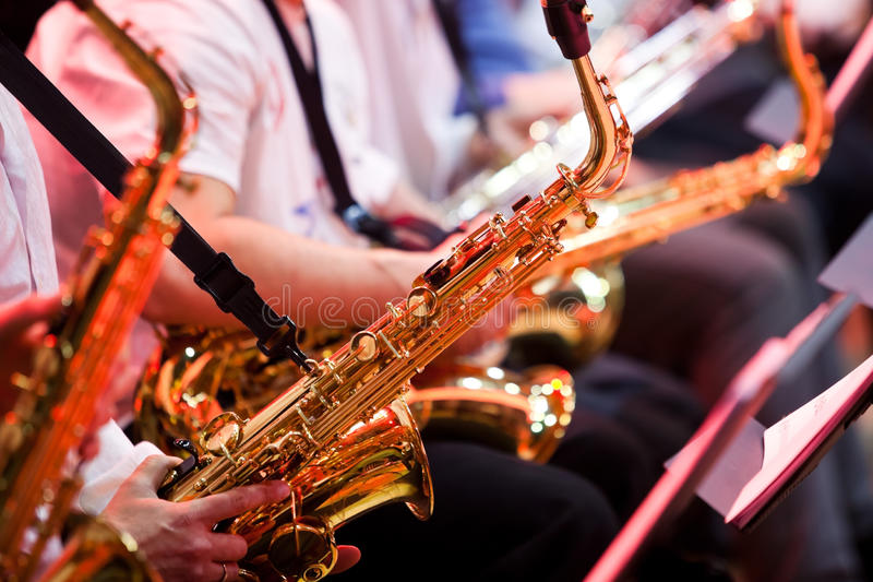 Saxophone in the hands of a musician. In an orchestra closeup royalty free stock image