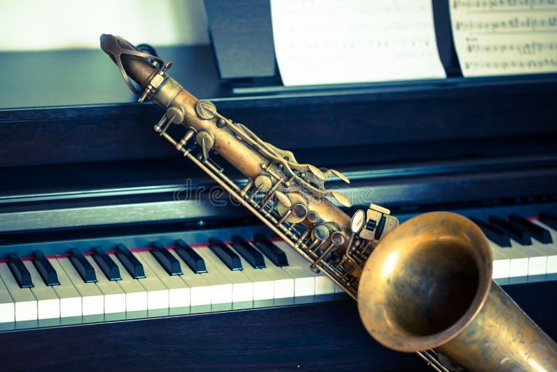 Saxophone on piano stock photo