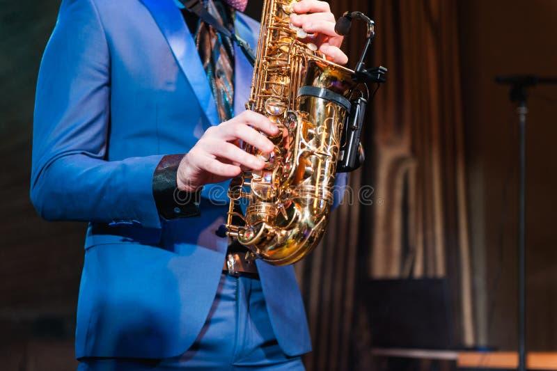Saxophone player jazz music instrument Saxophonist. With Baritone sax closeup on black royalty free stock photos