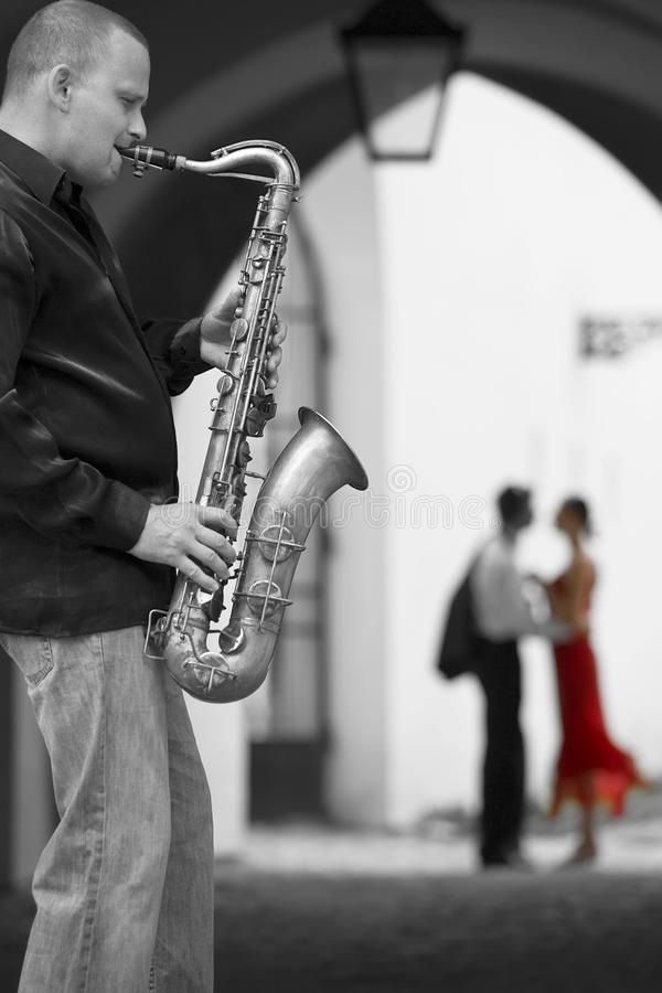 Saxophone Player With Romantic Couple. Black and white photograph street musician playing his saxophone while a romantic couple can be seen out of focus in the royalty free stock image