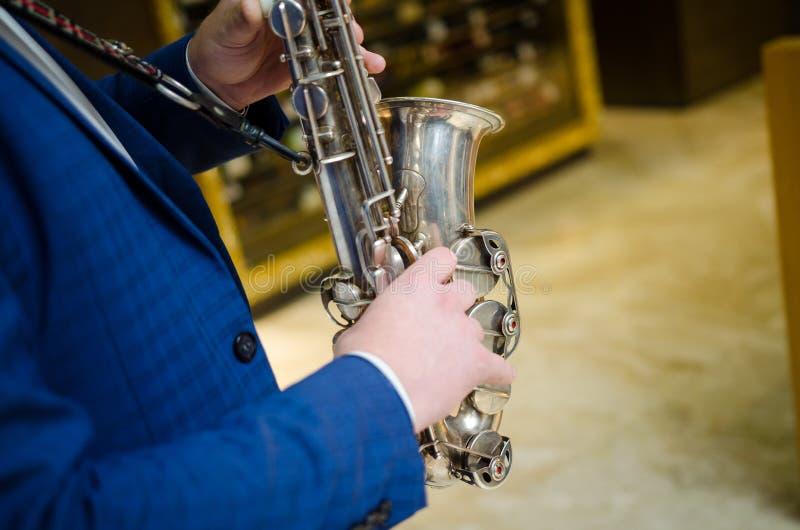 Saxophone player. Saxophonist hands playing saxophone. Alto sax player with jazz music instrument closeup.  stock photos