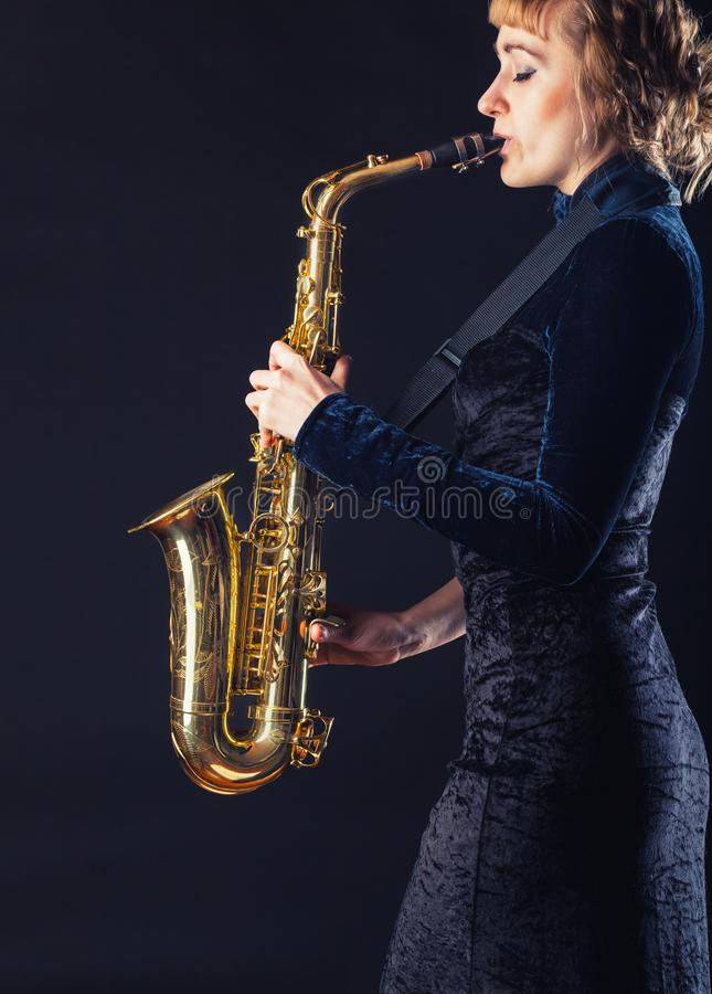 Saxophone. Player. Woman with  against a dark background royalty free stock photos