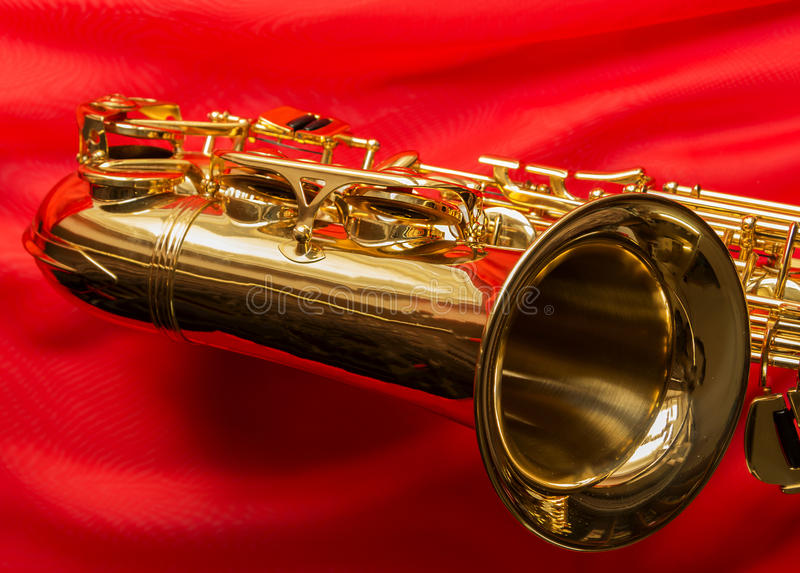 Saxophone on a red silk. Beautiful golden saxophone on delicate red silk background stock image