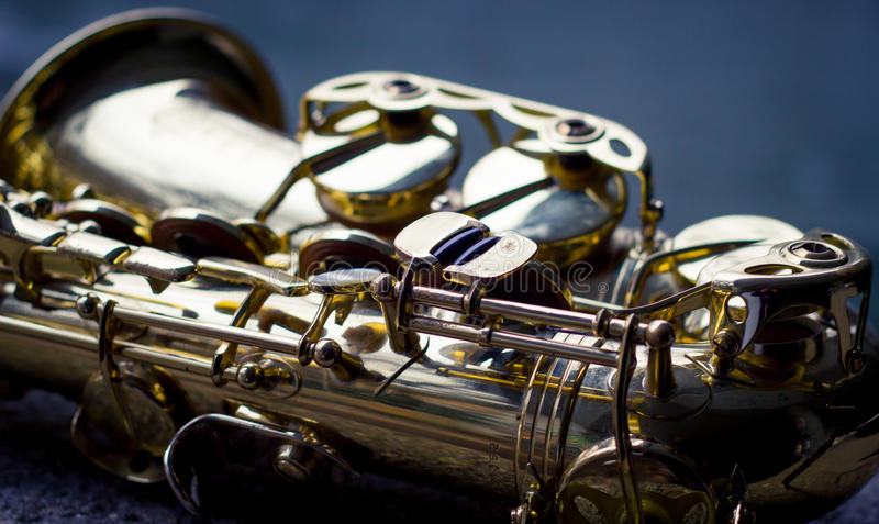 Saxophone by the river. Saxophone lying in front of a blue river royalty free stock images