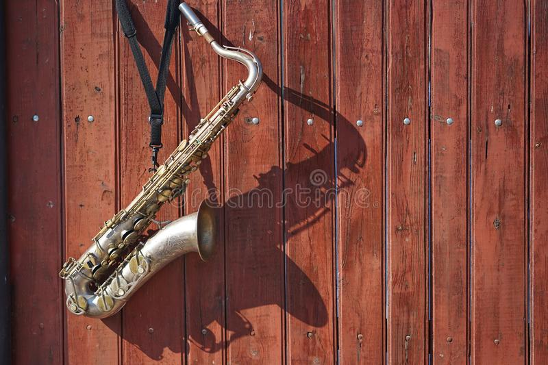 Saxophone still life. Still life with closeup of a saxophone hanging on a wooden fence stock photo