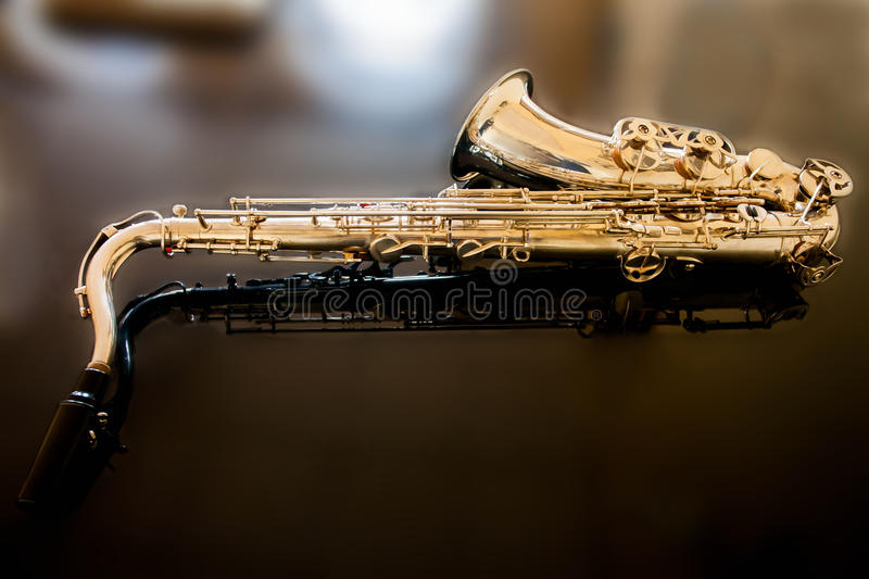 Saxophone tenor. Woodwind Classical Instrument. Jazz, blues, classics. Music. Saxophone on a black background. Black mirror surfac. Musical instrument saxophone stock images