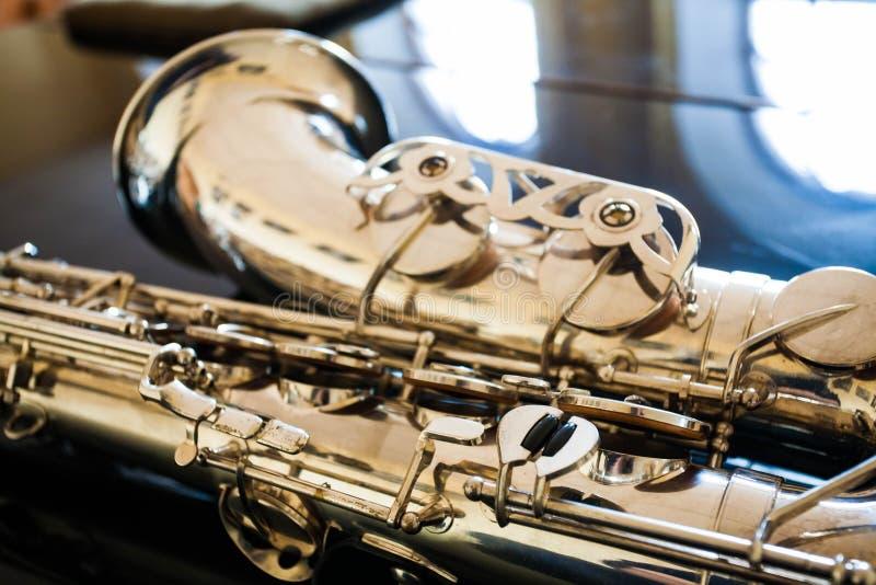 Saxophone tenor. Woodwind Classical Instrument. Jazz, blues, classics. Music. Saxophone on a black background. Black mirror surfac. Musical instrument saxophone stock image