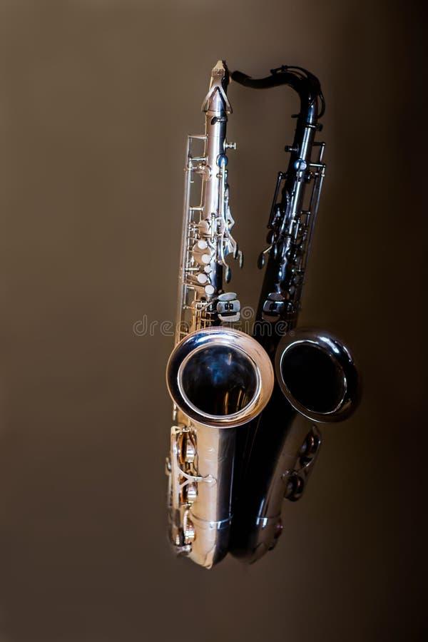 Saxophone tenor. Woodwind Classical Instrument. Jazz, blues, classics. Music. Saxophone on a black background. Black mirror surfac. Musical instrument saxophone stock photography