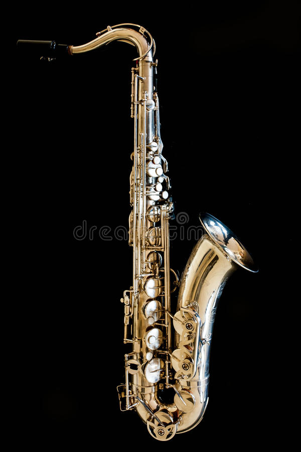 Saxophone tenor. Woodwind Classical Instrument. Jazz, blues, classics. Music. Saxophone on a black background. Black mirror surfac. Musical instrument saxophone royalty free stock image