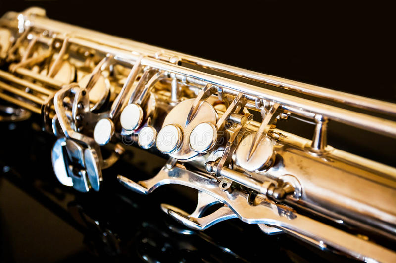 Saxophone tenor. Woodwind Classical Instrument. Jazz, blues, classics. Music. Saxophone on a black background. Black mirror surfac. Musical instrument saxophone royalty free stock photography
