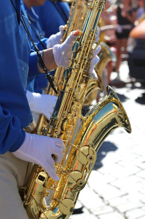 Saxophones and the saxophonist with white gloves. Music band with many saxophones and the saxophonist with white gloves playing the musical instrument royalty free stock images