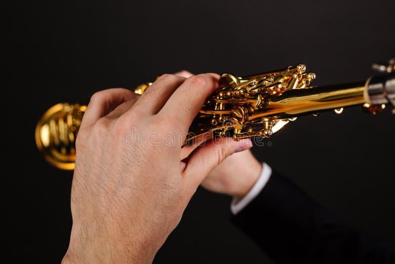 Saxophonist σε ένα μαύρο κλασικό κοστούμι που παίζει το saxophone σοπράνο σε μια μαύρη πλάγια όψη υποβάθρου στοκ φωτογραφίες με δικαίωμα ελεύθερης χρήσης