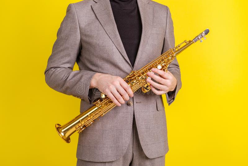 Saxophonist στα κλασικά ενδύματα που κρατά ένα saxophone σοπράνο σε μια κίτρινη κινηματογράφηση σε πρώτο πλάνο υποβάθρου στοκ εικόνες