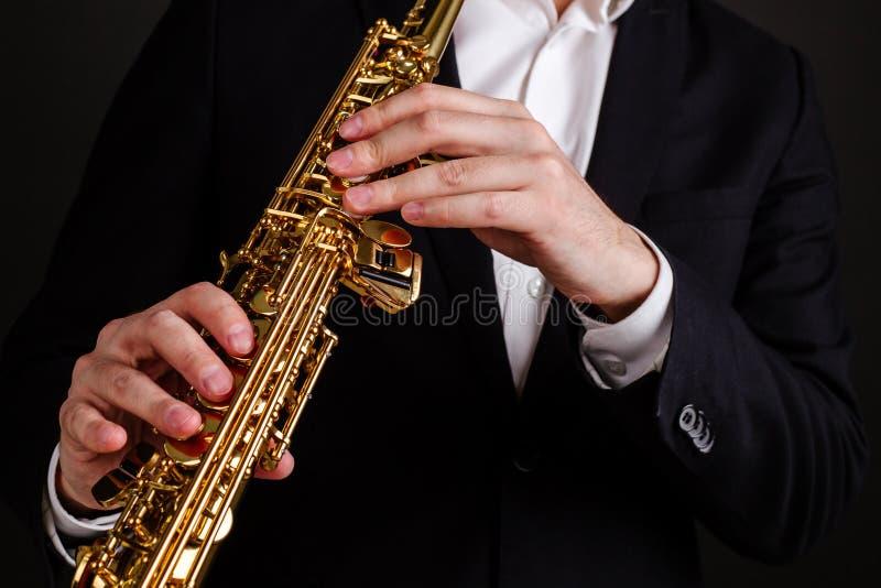 Saxophonist στο μαύρο κλασικό saxophone σοπράνο παιχνιδιού κοστουμιών στην κινηματογράφηση σε πρώτο πλάνο ορχηστρών τζαζ στοκ εικόνες