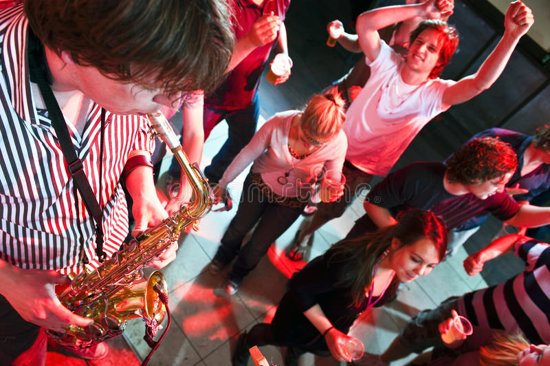 Saxophonist. Playing in a nightclub, with dancing people in the background royalty free stock photography