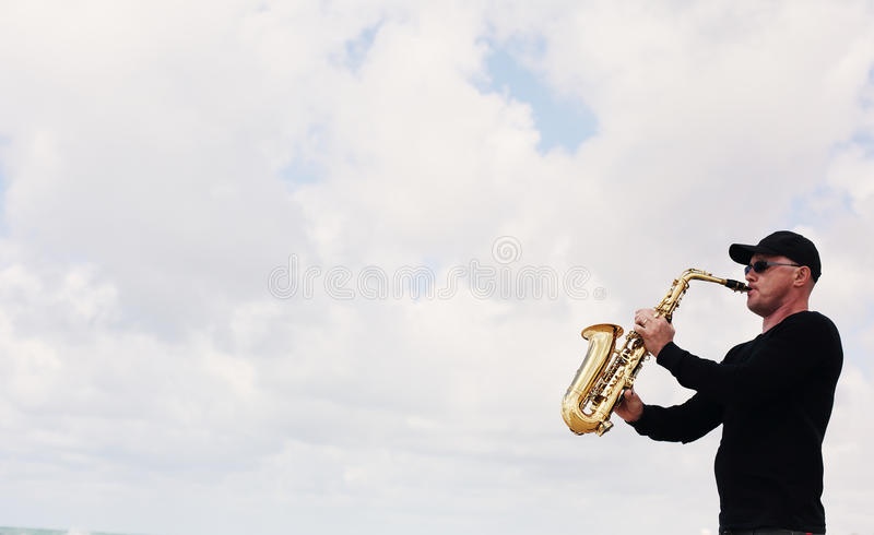 Saxophonist, der auf dem Saxophon im Freien spielt lizenzfreie stockfotos