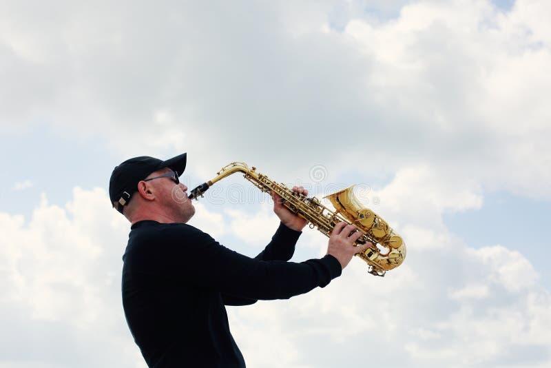 Saxophonist, der auf dem Saxophon im Freien spielt stockbild