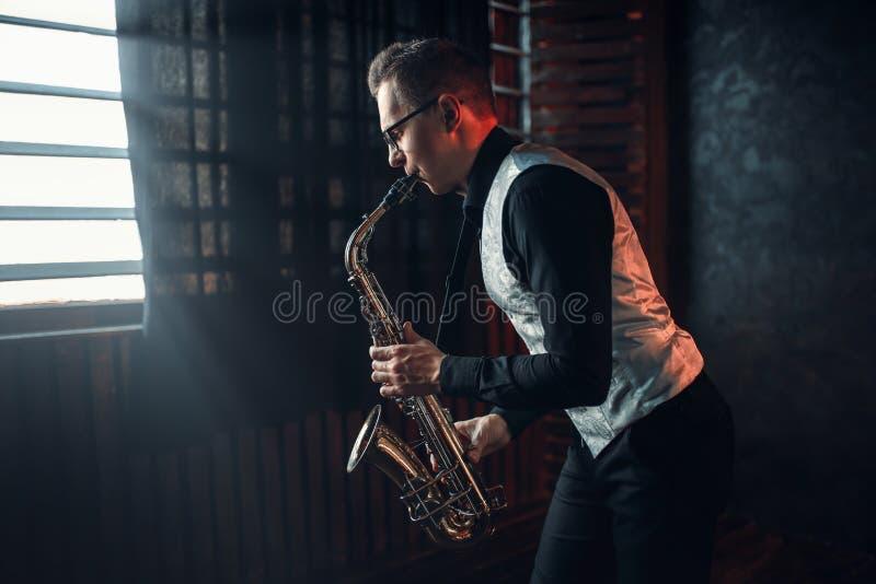Saxophonist, der Jazzmelodie auf Saxophon spielt stockfotos
