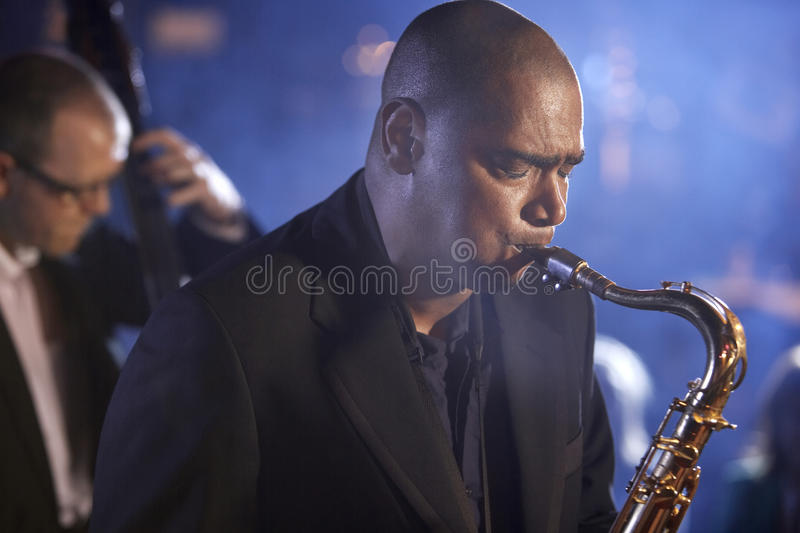 Saxophonist And Double Bass Player Performing In Jazz Club stock image